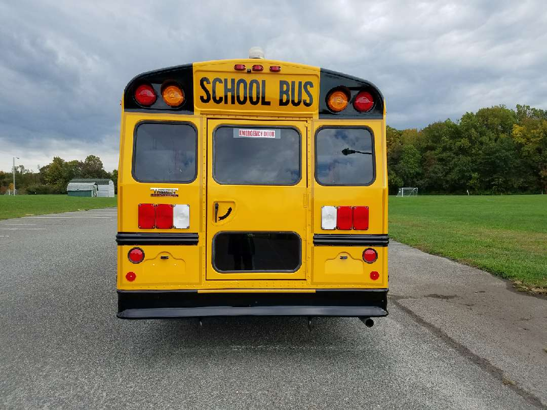Rear of school bus showing the emergency door and tail lights