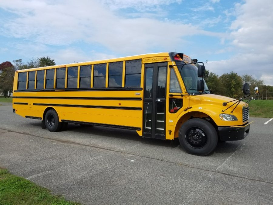 Side view of a school bus with the folding doors