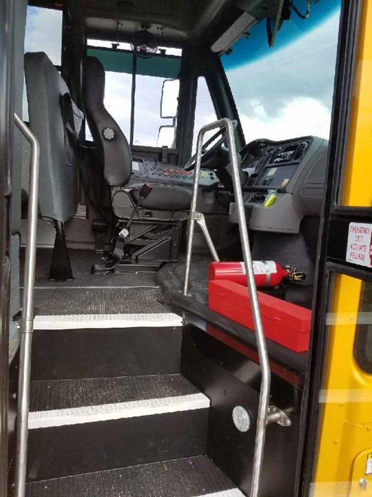 Entrance to a Thomas bus showing steps and the drivers seat